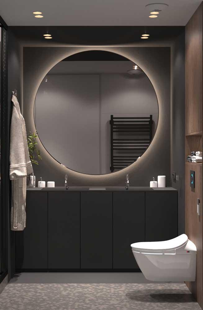 O banheiro moderno ganhou um enorme espelho redondo com iluminação em led atrás da peça