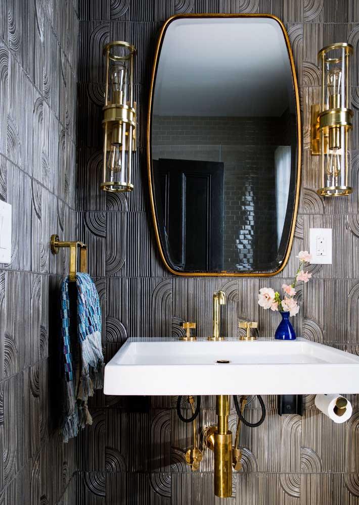 O detalhe da moldura dourada do espelho para banheiro se harmoniza com os metais no mesmo tom