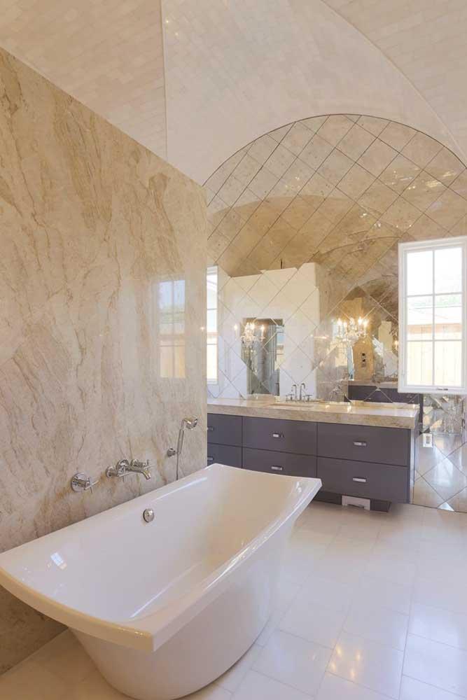 O banheiro em mármore ganhou um espelho desenhado que quase toma a parede por inteiro