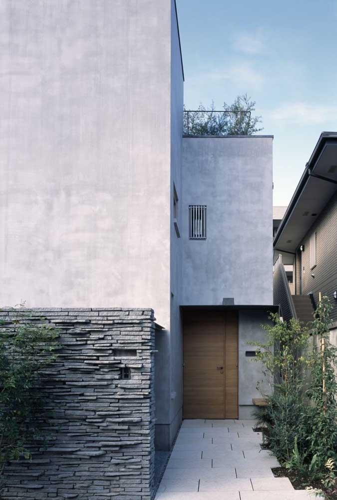 Pedra canjiquinha e cimento queimado se unem para criar uma fachada de casa simples com um pé no rústico e outro no moderno
