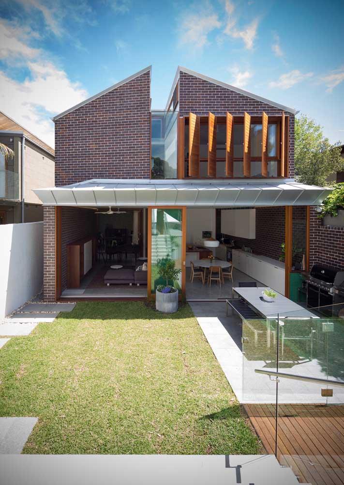 Casa pequena e moderna com fachada de tijolinhos, madeira e vidro