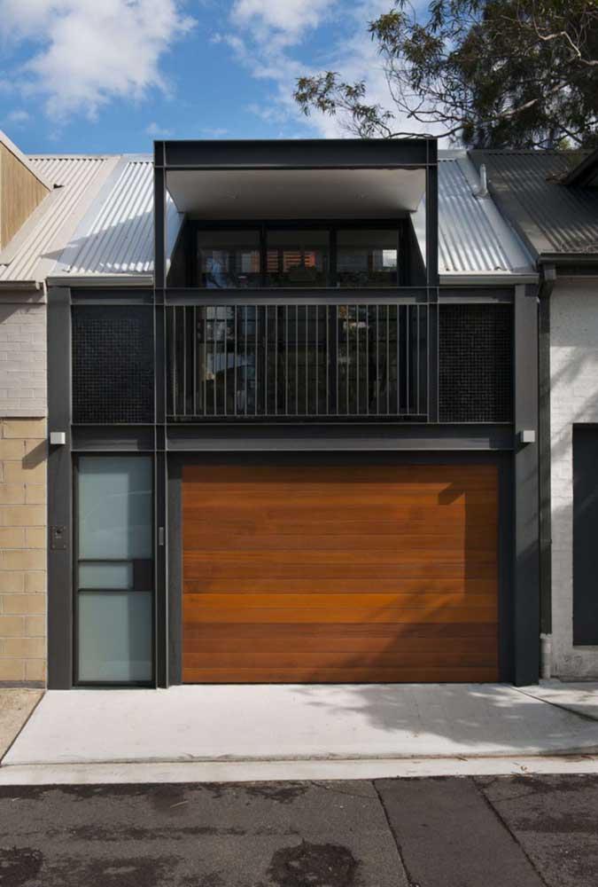 Fachada de casa simples e moderna com portão da garagem em madeira