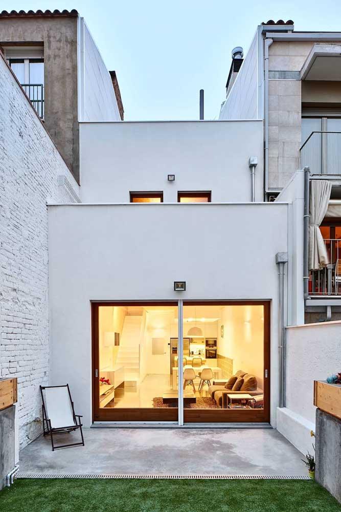 Os frisos de madeira se destacam em meio as paredes brancas dessa fachada