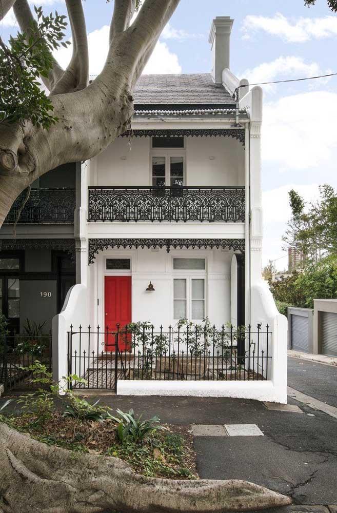 Fachada simples, de casa em estilo clássico; o grande destaque vai para a porta pintada de vermelho e para as grades de ferro lindamente desenhadas