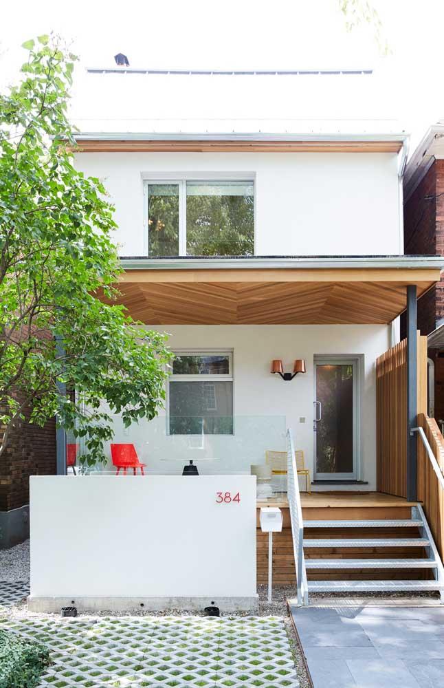 Fachada de casa pequena com varanda; os detalhes em madeira são o destaque desse projeto