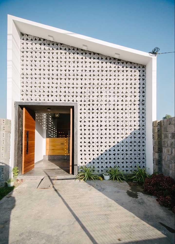 Fachada de casa pequena com destaque para a parede de cobogos e a porta larga modelo pivotante em madeira