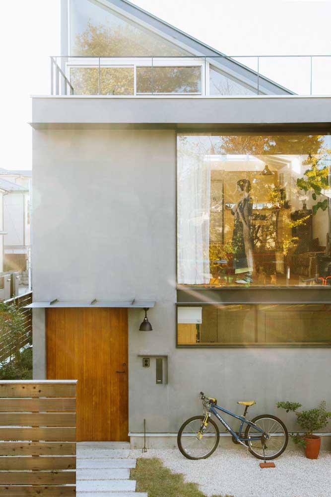 A grande abertura em vidro é o destaque dessa fachada simples e pequena