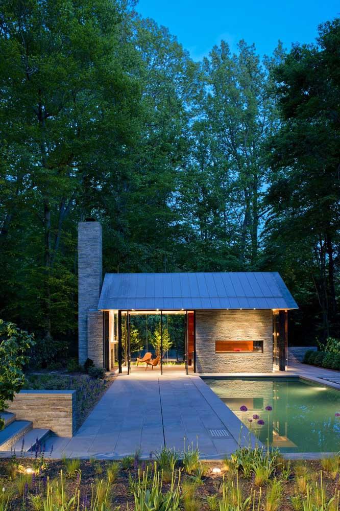 Em meio à natureza, essa casa pequena e simples toda revestida com pedras chama a atenção