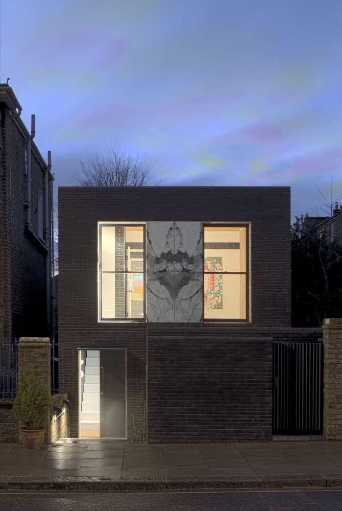 Nessa fachada moderna com tijolinhos à vista, o destaque vai para o painel de porcelanato