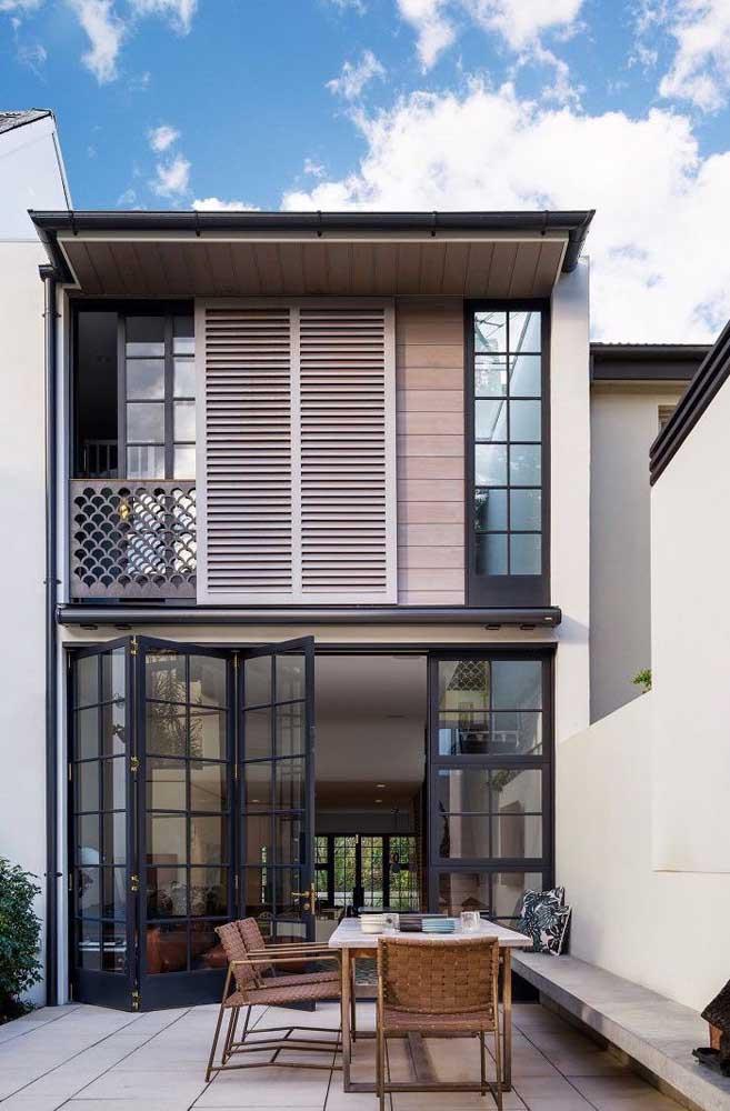 Porta dobrável de vidro e espaço gourmet externo: os dois pontos de maior destaque nessa fachada