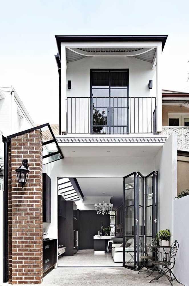 Fachada de casa simples com porta de vidro; a pintura branca em contraste com os detalhes pretos é um charme à parte