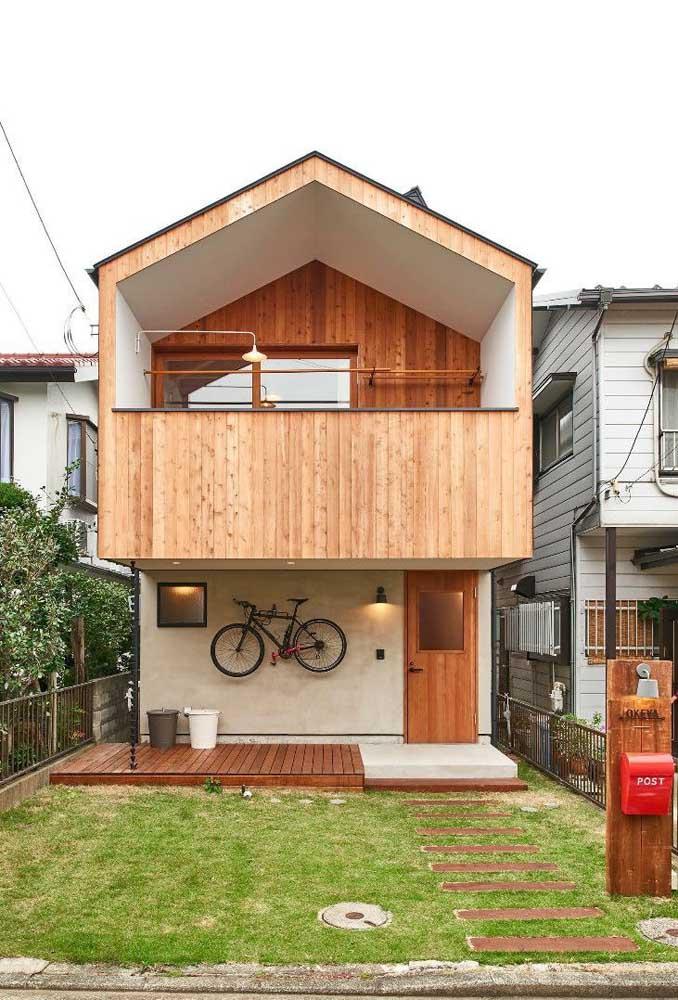 Essa outra pequena casa conta com revestimento de madeira para completar a estética da fachada