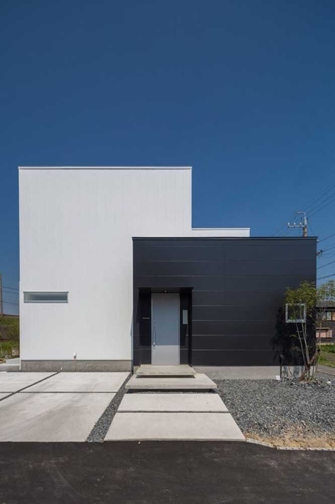 Fachada de casa pequena e moderna; repare que parte dela foi revestida com chapas metálicas na cor preta