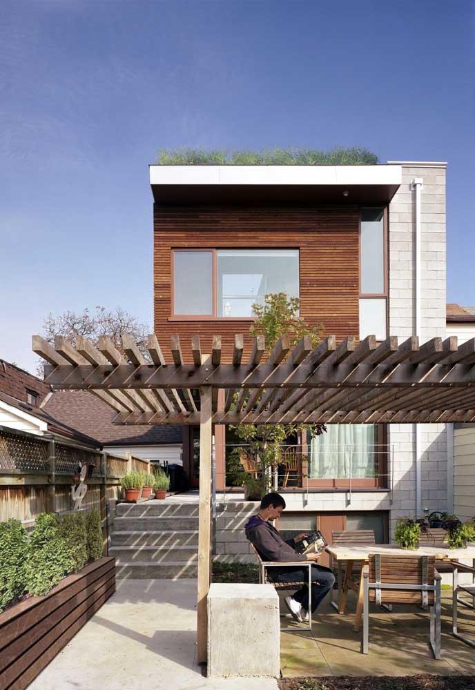 Fachada de casa simples com pergolado de madeira; a estrutura garante um toque de conforto e acolhimento à entrada da residência