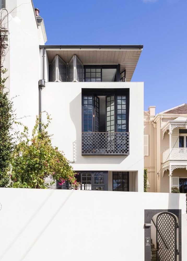 Fachada de casa simples branca; repare que a prioridade aqui foi no uso de janelas para garantir a luminosidade no interior da residência