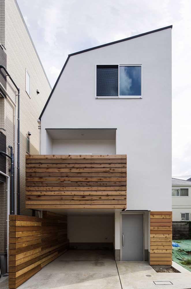 Fachada de casa pequena com varanda e garagem; o destaque aqui vai para o revestimento de madeira