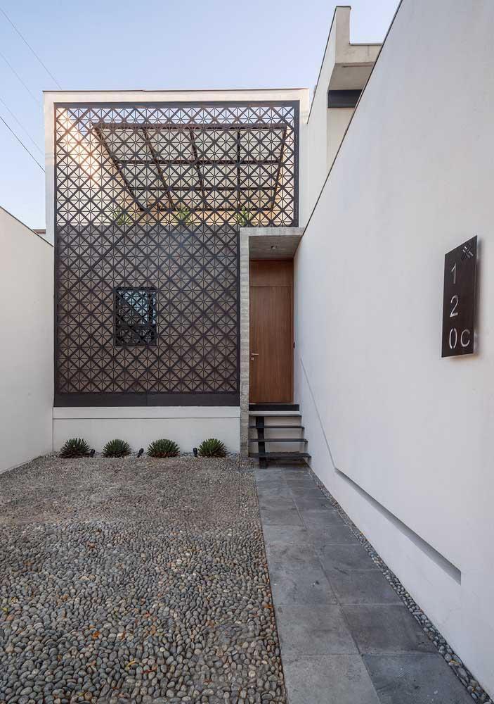 Nessa fachada simples, o espaço da garagem é sobre as pedras