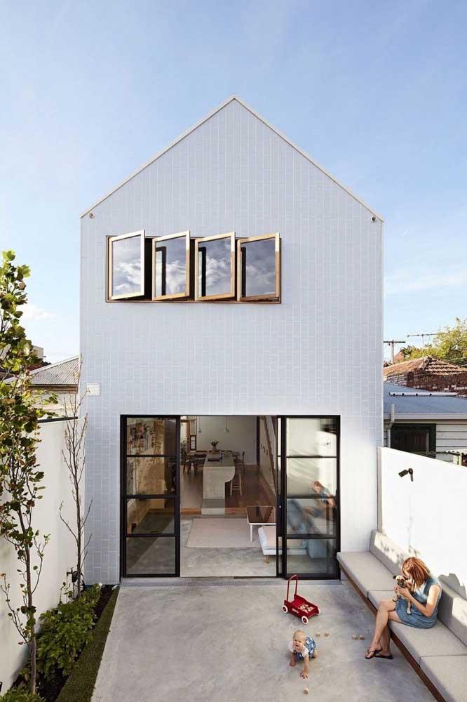 Essa fachada de casa simples evidencia o uso do vidro e a preferência por uma iluminação natural na parte interna da casa