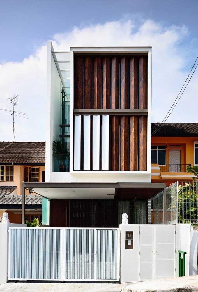 Fachada de casa pequena com telhado embutido; destaque para o uso da madeira em combinação com o vidro