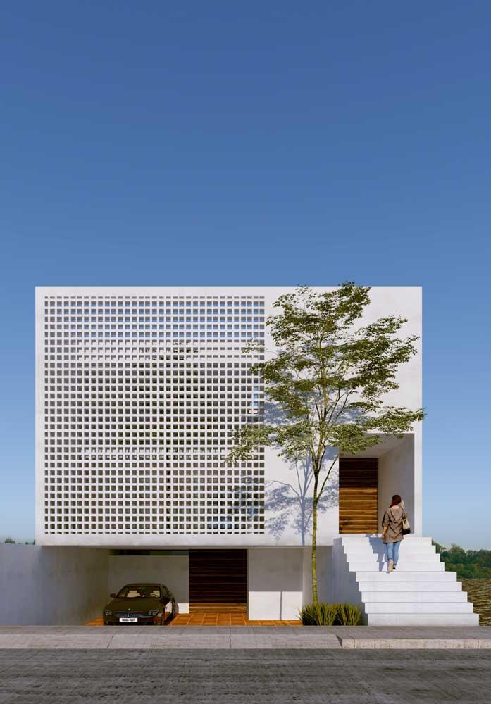 A frente dessa casa super moderna traz uma fachada vazada e o uso do branco como cor principal