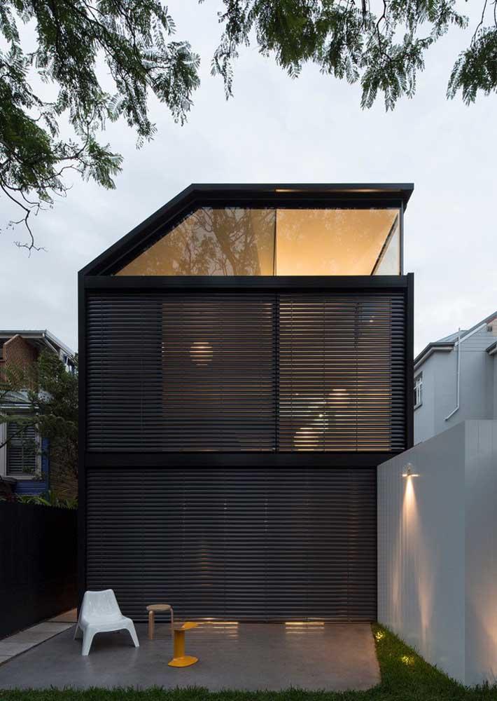 A fachada moderna com ripas de madeira preta deixa transparecer a iluminação acolhedora do lado interno da residência, resultando em um efeito visual muito bonito