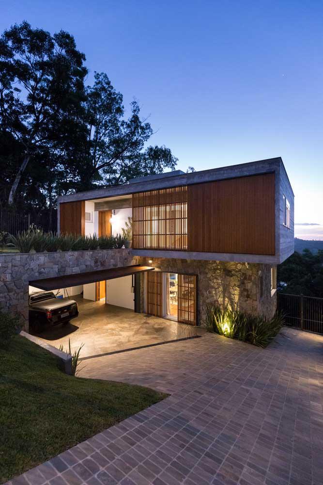 Casa moderna, luxuosa, mas com um toque rústico e acolhedor, graças ao uso da pedra e da madeira na fachada
