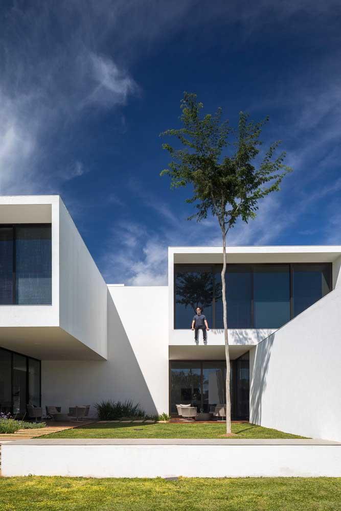 Fachada de casa moderna, branca, com grandes aberturas de vidro e um jardim de grama