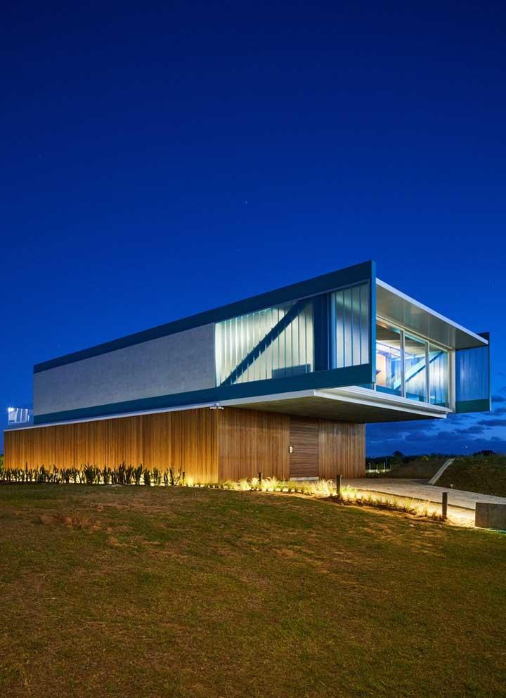 Nessa outra fachada moderna, a madeira forra o primeiro pavimento, enquanto o concreto e o vidro tomam conta do segundo