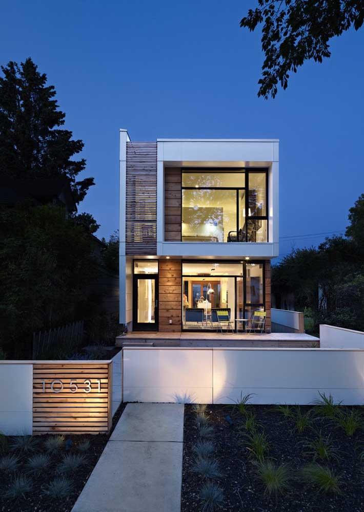Sobrado com fachada moderna; destaque para o projeto de iluminação que valoriza a entrada da casa à noite
