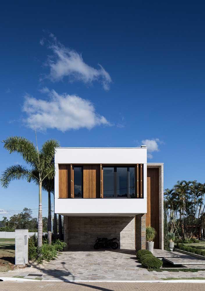 Fachada de casa moderna com janelas de madeira e revestimento de pedra