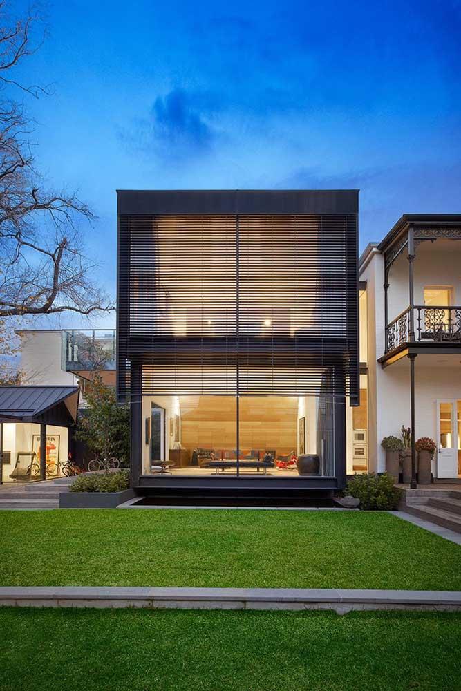 Nessa fachada moderna, as ripas de madeira tem função semelhante a uma persiana