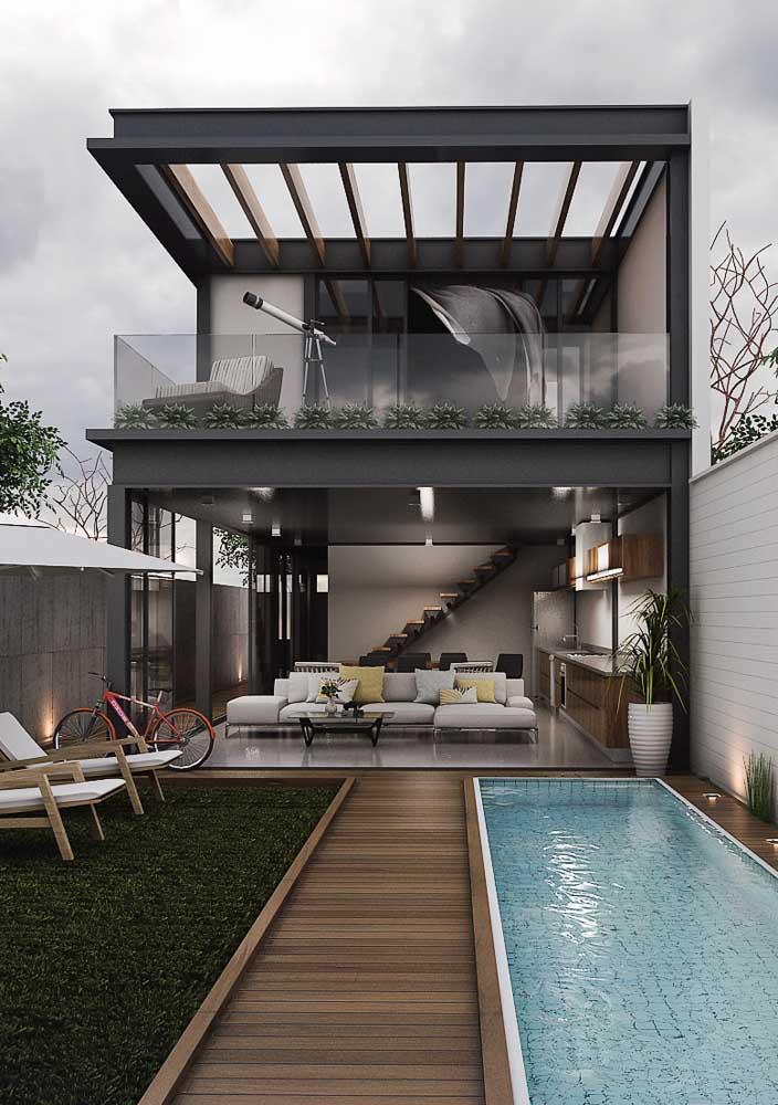 Fachada de casa moderna com pergolado e aberturas de vidro que revelam o interior da casa
