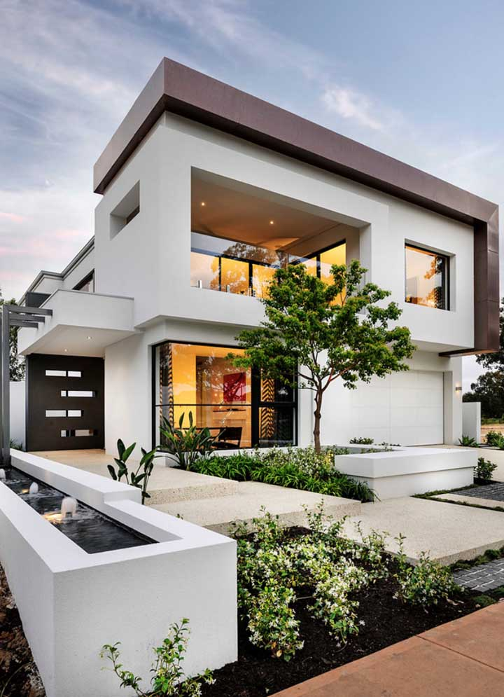 Fachada de casa moderna grande com mini lago e jardim para completar o visual externo