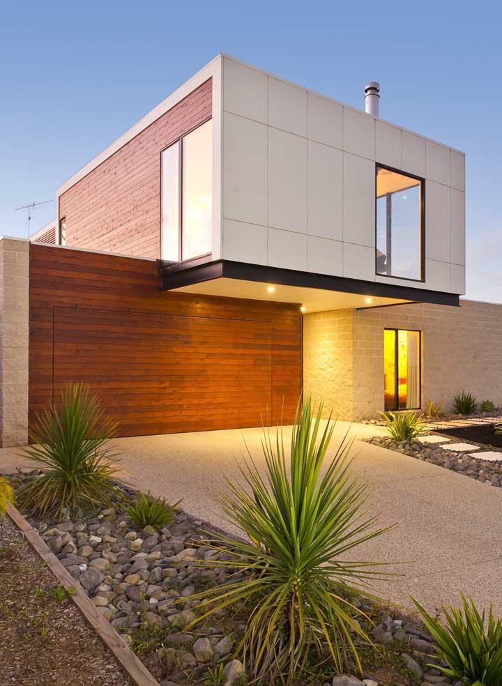Já essa outra casa moderna, apostou em uma fachada com jardim de estilo rústico e desértico