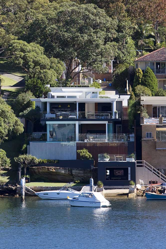Na beira do lago, a casa moderna é emoldurada pela beleza natural da paisagem