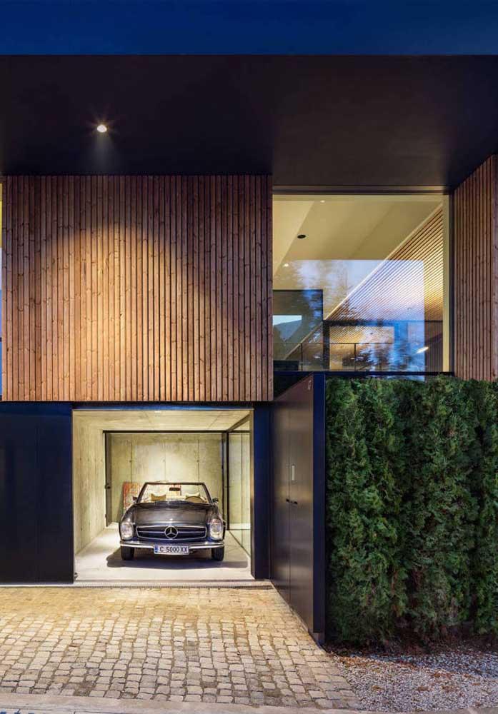 Fachada de casa moderna com garagem; o tom escuro de azul em combinação com a madeira são o grande diferencial