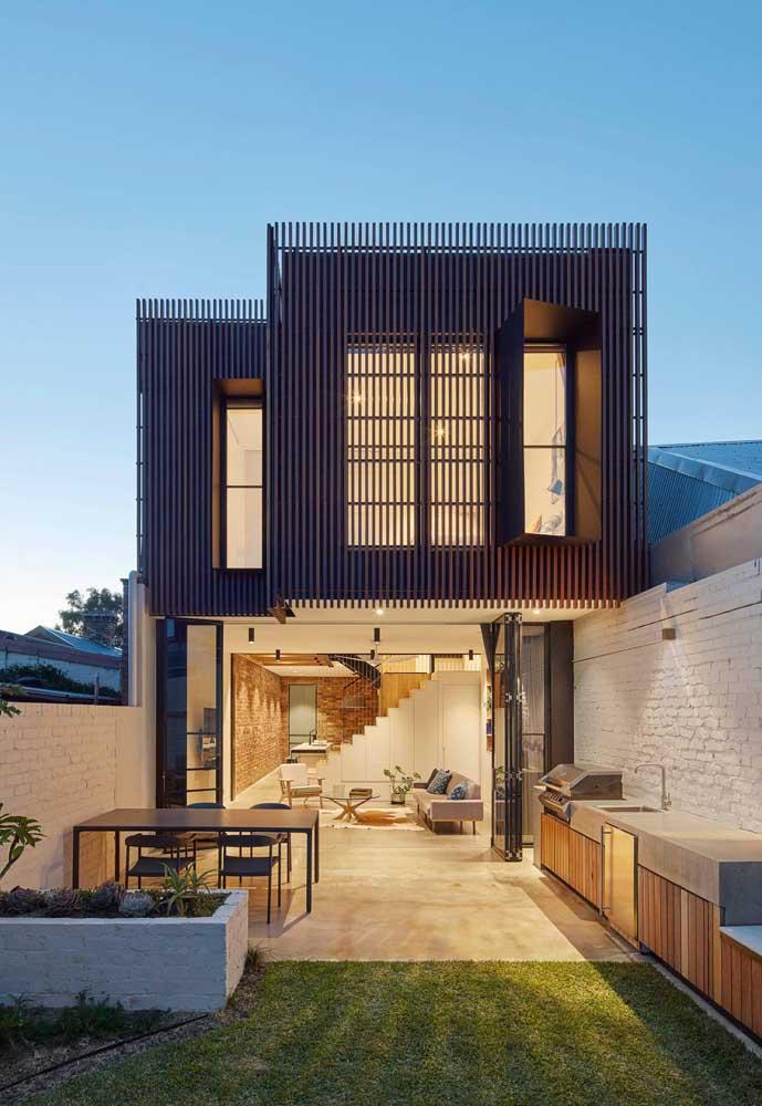 Fachada de casa moderna com revestimento na parte superior que se assemelha a treliças metálicas