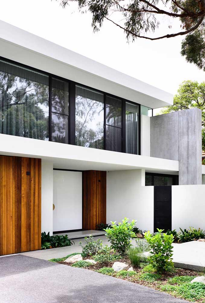 Típico modelo de fachada moderna: linhas retas, uso do vidro e cores como o branco e preto, além da madeira