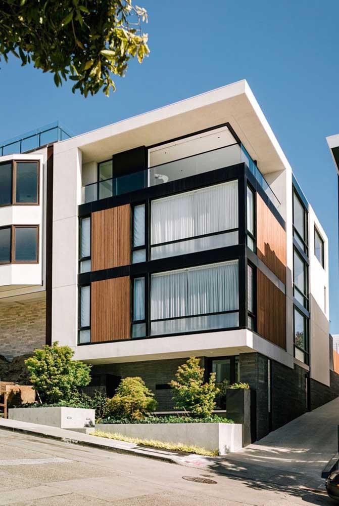 Com três pavimentos, a fachada da casa moderna conta com a clássica dupla preto e branco e elementos em madeira