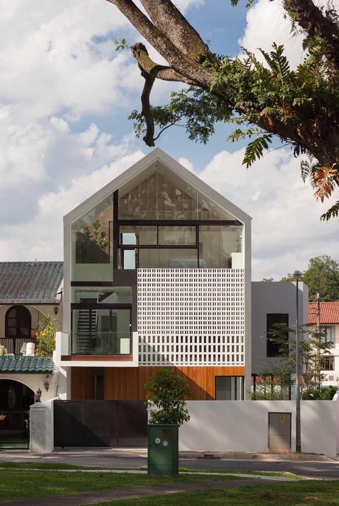 O telhado duas águas faz uma referência às casas clássicas e tradicionais, mas o uso do vidro e dos revestimentos logo revela a inspiração moderna