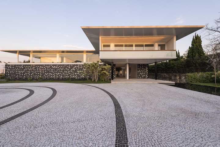 Fachada de casa moderna e imponente com destaque para o muro de revestimento preto e branco