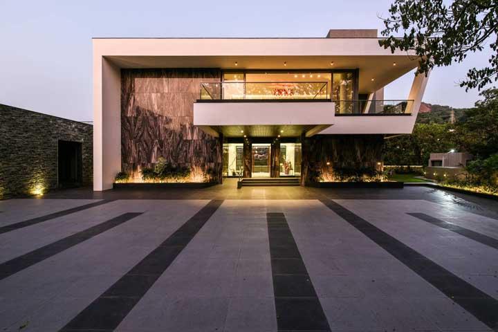 Nessa fachada moderna, o porcelanato foi o material escolhido para revestir as paredes externas e criar a impressão de um mármore