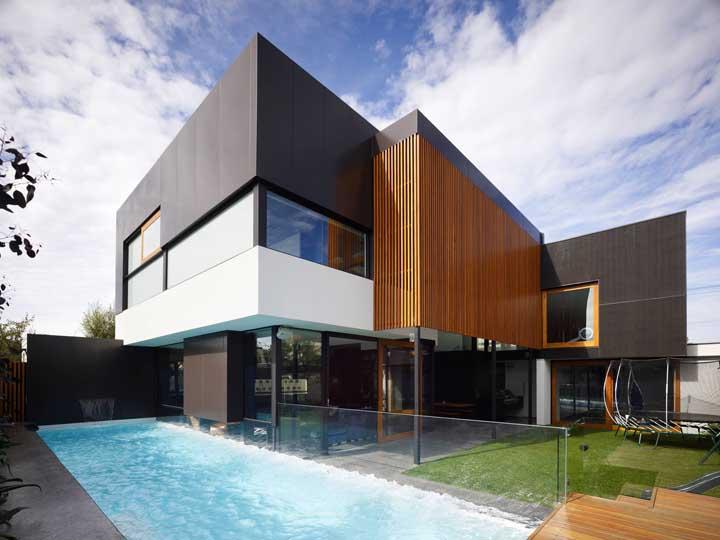 Fachada de casa moderna com piscina e o uso das cores preferidas para esse tipo de projeto: o preto e o branco