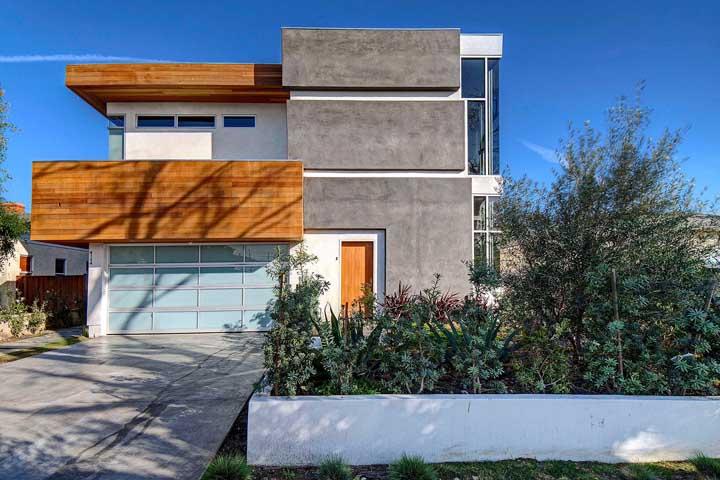 Cimento queimado, madeira e vidro mais uma vez mostram sua versatilidade em um projeto de fachada de casa moderna