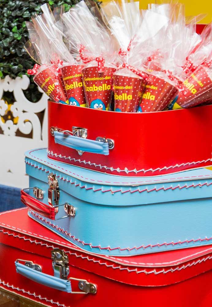 O que acha de organizar as lembrancinhas dentro de malas de viagem?