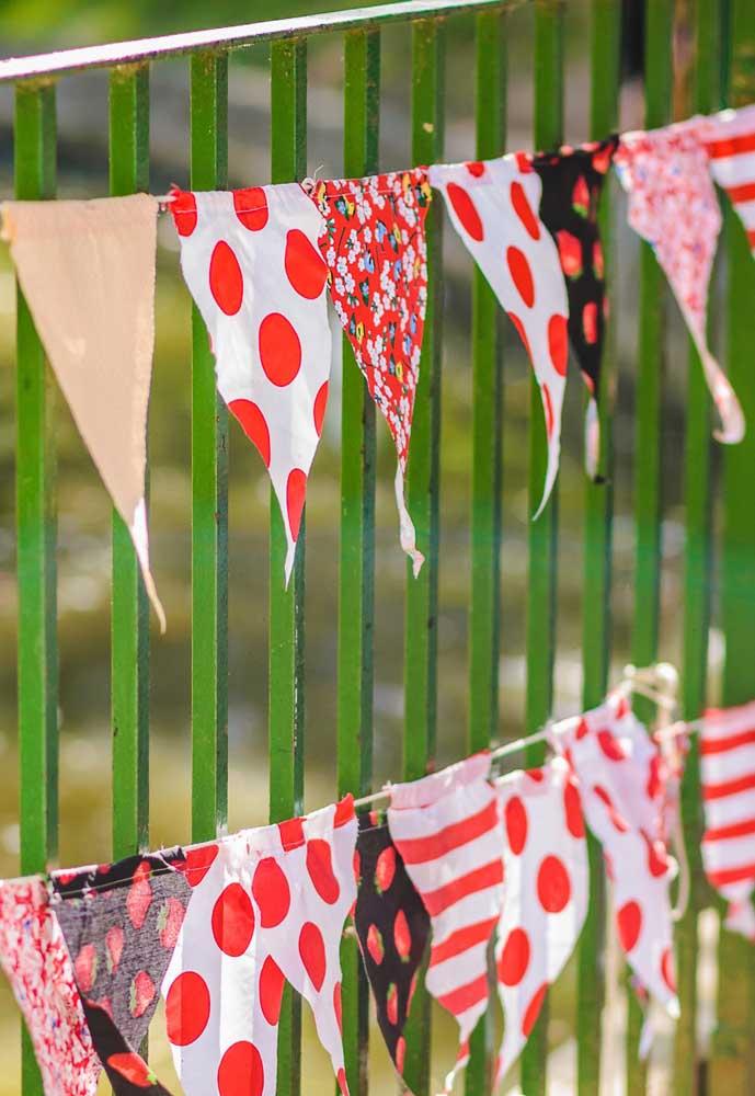 Corte pedaços de tecidos com estampas diferentes e faça um varal de bandeirinha.