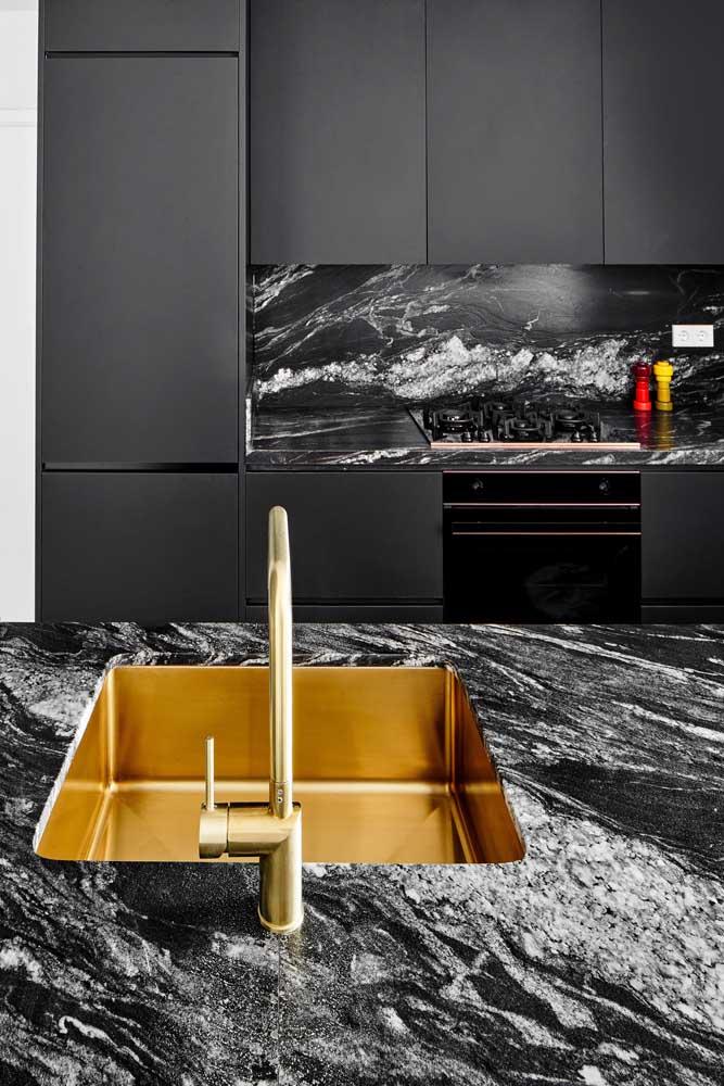 Uma cozinha incrível revestida com granito preto Indiano na bancada da pia e na placa entre os armários e o fogão