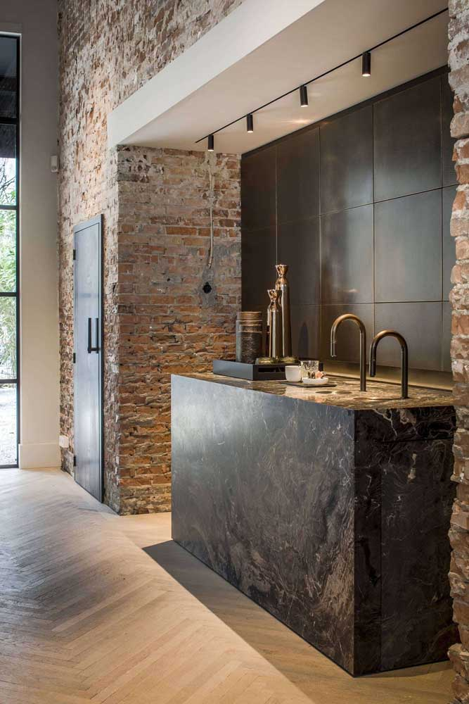 A ilha da cozinha ficou muito elegante revestida com granito preto indiano; repare no contraste formado com a parede de tijolinhos