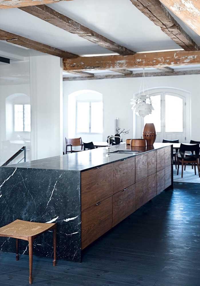 A combinação entre o preto do granito com a madeira dos armários ficou incrível nessa cozinha