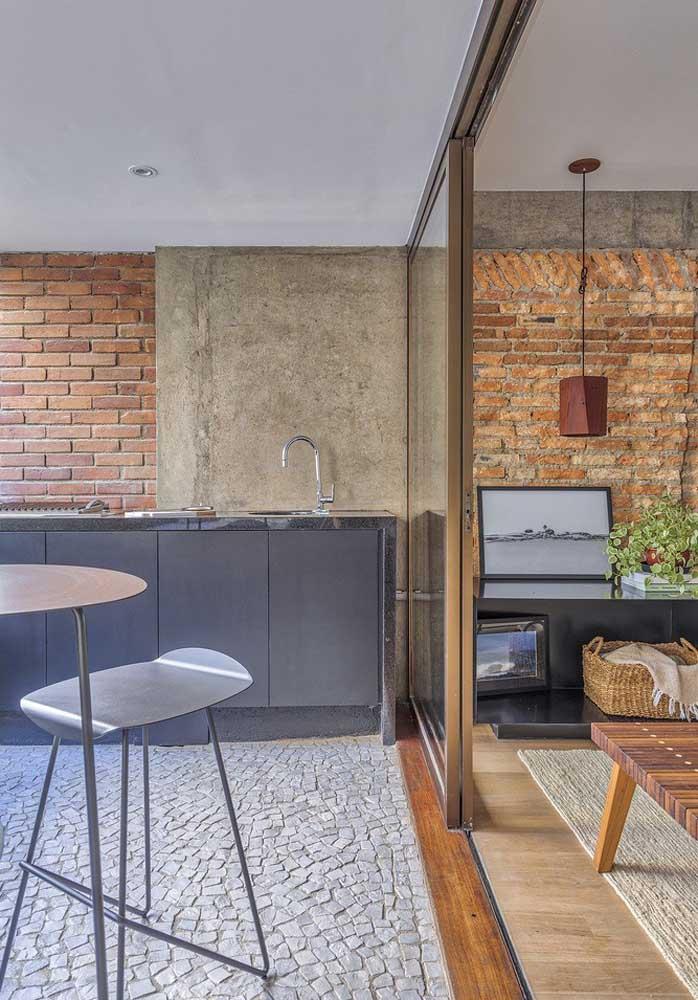 Aqui, podemos observar como o granito é versátil e pode ser usado em diferentes ambientes: nessa imagem, ele entra na bancada do espaço gourmet e na estante da sala de estar